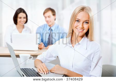 Closeup portrait of attractive business woman smiling with colleagues working in background