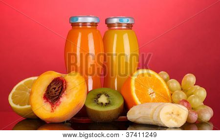 Delicious multifruit juice in a bottle and fruit next to it on pink background