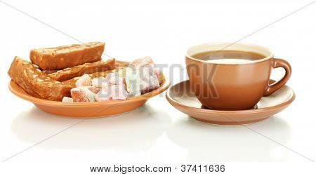 A cup of tea with a delicious turkish delight and sherbet on the plate isolated on white