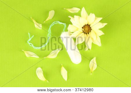 cotton tampon with yellow flower on green background close-up