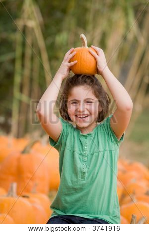 Little Girl Playing With A Pumpkin