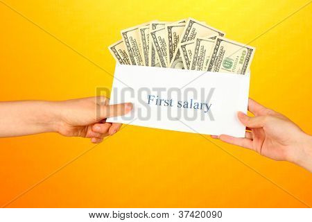 Woman's hand passes the envelope with the salary on yellow background