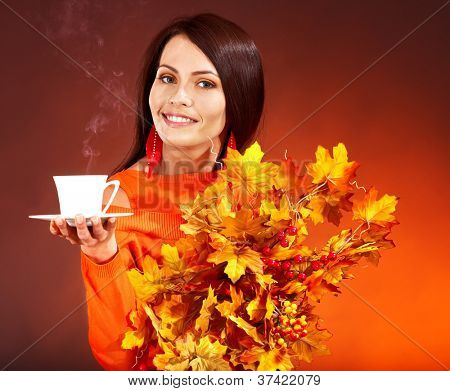 Woman holding  cup of coffee and orange leaves.