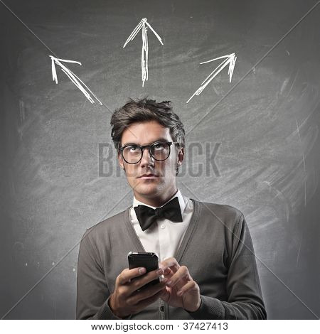 Fashionable man thinking while using a mobile phone