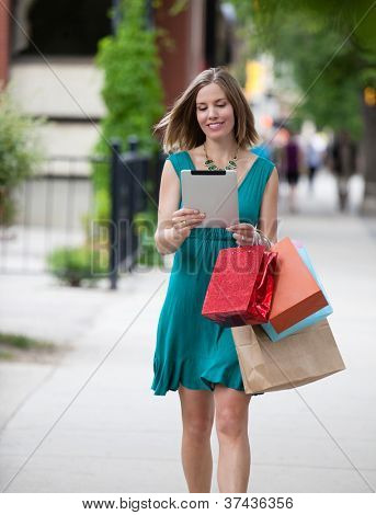 Shopping Woman holding Digital Tablet on street.
