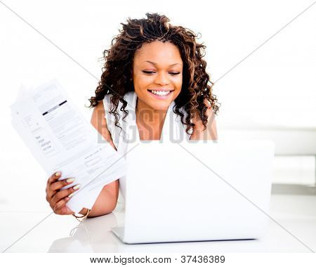 Woman paying bills online from home and smiling