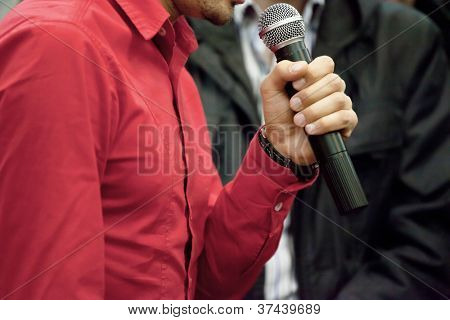 The image of man hand with microphone. Focus is under the microphone