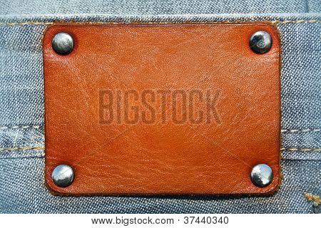 Blank leather label over blue jeans background with metal rivets