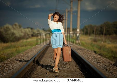 Young fashion girl with suitcase railways.