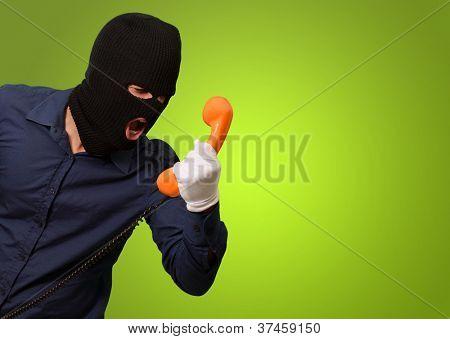 Einbrecher-Mann, hält Telefon auf grünem Hintergrund