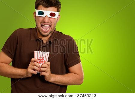 Young Man Wearing 3d Glasses And Holding Popcorn On A Green Background