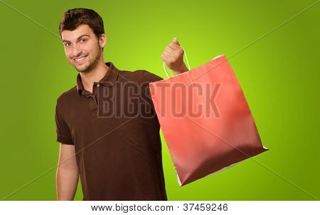Portrait Of A Young Man Holding Shopping Bag On Green Background