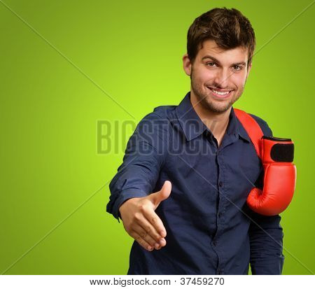Young Man With Boxing Glove On Shoulder Shaking Hand Isolated On Green Background