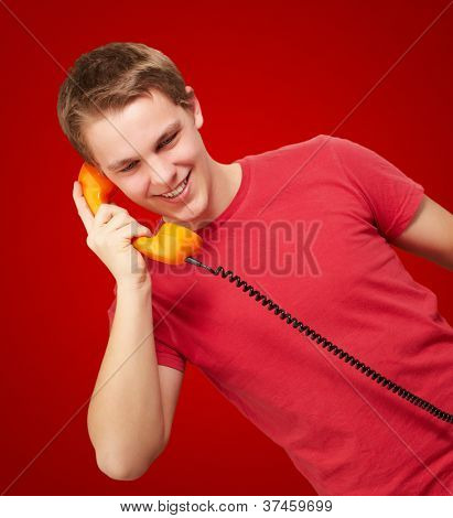portrait of young man talking on vintage telephone over red background