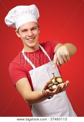 portrait of young cook man pressing a golden bell over red background