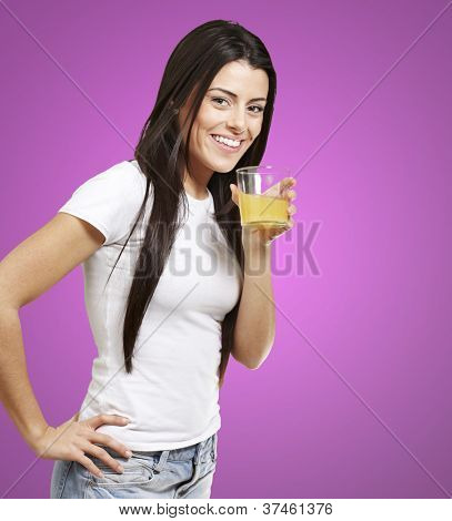 woman holding a glass of orange juice against a pink background