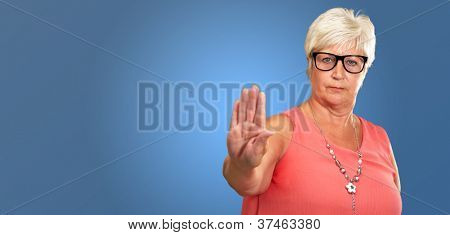 Portrait Of A Senior Woman Showing Stop Sign On Blue Background
