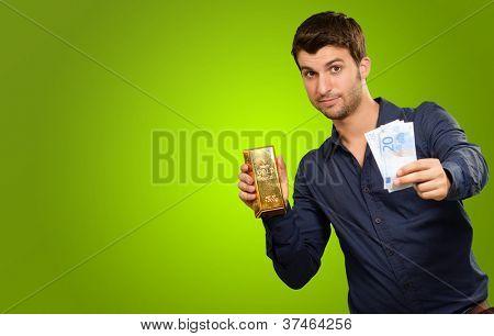 Hombre joven de moneda de tenencia y barra de oro sobre fondo verde