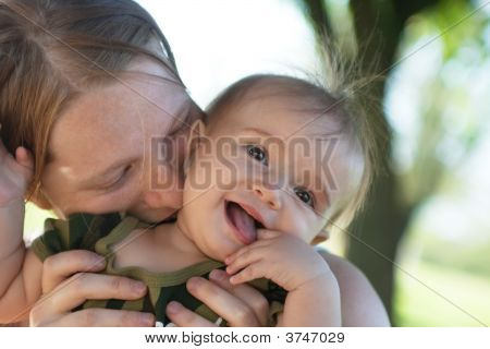 Mother Kissing Baby Girl In Her Neck