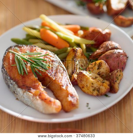 Salmon steak dinner with herbs and roasted potatoes.