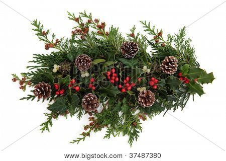 Winter and christmas decorative floral arrangement of holly with red berry clusters, mistletoe, ivy and cedar leaf sprigs with pine cones over white background.