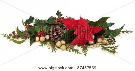 Christmas decorative floral arrangement of a poinsettia flower, holly, mistletoe, ivy, cedar cypress leaf sprigs, pine cones and gold sparkling baubles over white background.