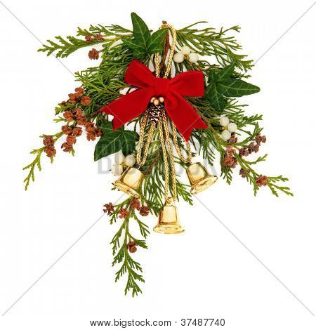 Christmas decorative spray of mistletoe, ivy, cedar leaf sprigs with pine cones and golden bells tied with a red velvet ribbon over white background.
