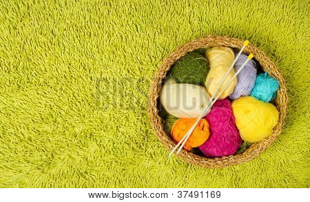 Knitting Yarn Balls And Needles In Basket Over Green Carpet Background