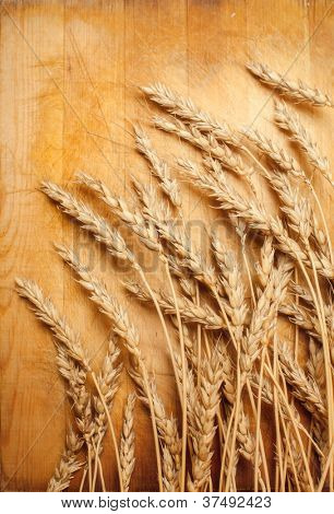 ears of wheat on a wooden surface