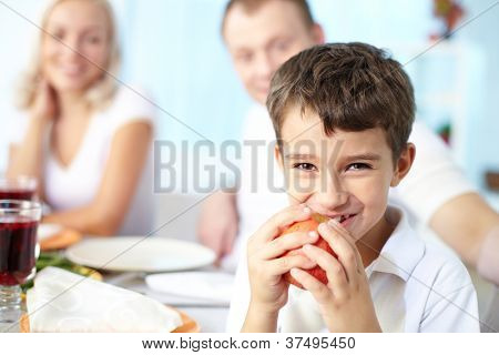 Portrait of happy boy with apple sitting at festive table and looking at camera with his parents on background