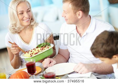 Portrait of happy couple and their son sitting at festive table