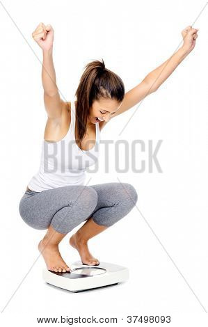 Hispanic woman celebrating and cheering a weightloss goal achievement isolated on white and on a scale