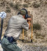 stock photo of cap gun  - Handgun shooter practicing while on the shooting range - JPG
