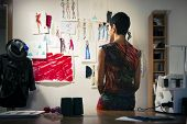 stock photo of mannequin  - Young people and small business hispanic woman at work as fashion designer and tailor looking at sketches of new collection in atelier - JPG