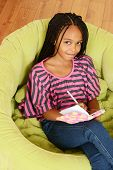 picture of cornrow  - Top view young girl writing in diary sitting in a green chair - JPG