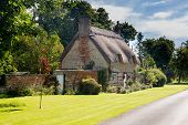 image of english cottage garden  - Ancient cotswold stone house and flower garden in Cotswold village of Honington - JPG