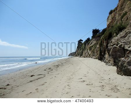 Waves Lap On The Beach Next To Tall Cliff In Santa Barbara, California.