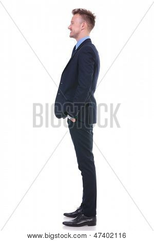 full length side view picture of a young business man with his hands in his pockets looking straight forward, away from the camera and smiling. on white background