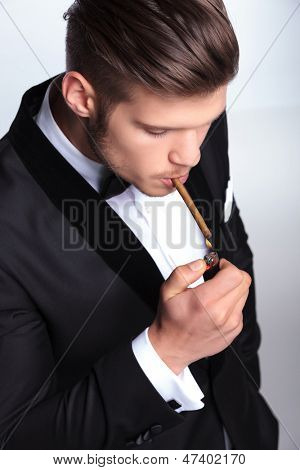 closeup picture of an elegant young fashion man in tuxedo lighting up his cigar. on gray background