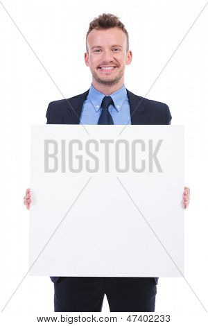 young business man holding a blank pannel with both hands and smiling at the camera. on white background