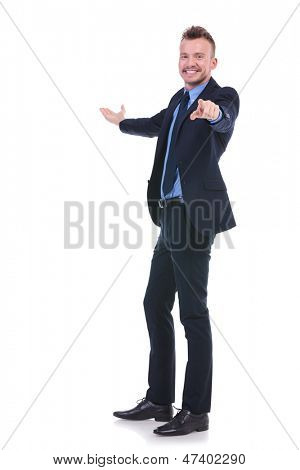 full length picture of a young business man presenting in the back while pointing and smiling at the camera. on white background