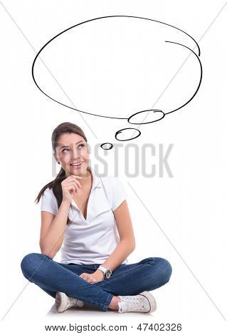 casual young woman sitting with legs crossed having a good idea, looking up at a speech bubble. isolated on white background