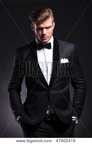 elegant young fashion man in tuxedo holding both his hands in his pockets while looking at the camera with a frowned expression. on black background