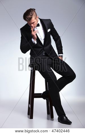 elegant young fashion man in tuxedo sitting on stool and smoking a cigar while looking down, away from the camera. on gray background