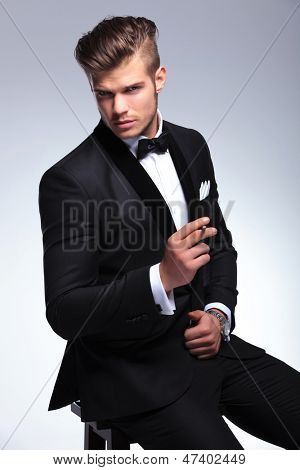 closeup of an elegant young fashion man in tuxedo sitting on a chair and holding a cigar while looking at the camera. on gray background