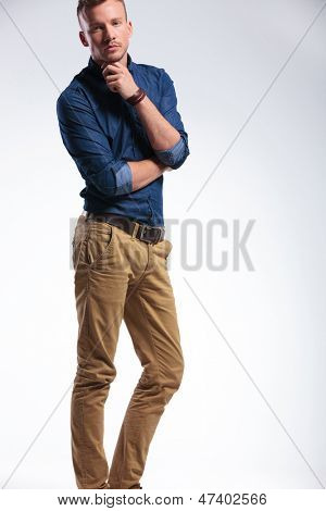 cutout picture of a pensive casual young man standing with his hand on his chin and looking at the camera. on gray background