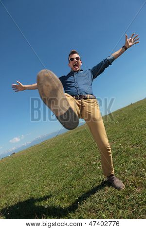 casual young man standing in a leg outdoor in the grass while holding his arms opened and screaming