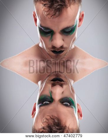 dual upside down mirror picture of a casual young man with dramatic makeup one with eyes closed and the other looking at the camera. on gray background