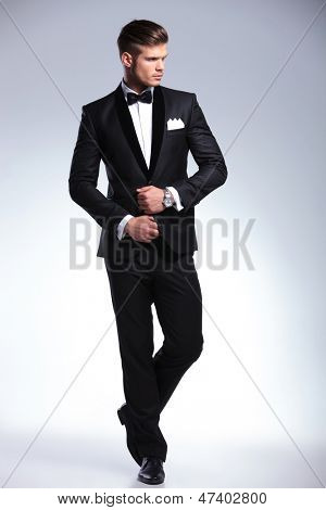 full length picture of an elegant young fashion man adjusting his tuxedo while looking to his side, away from the camera. on gray background