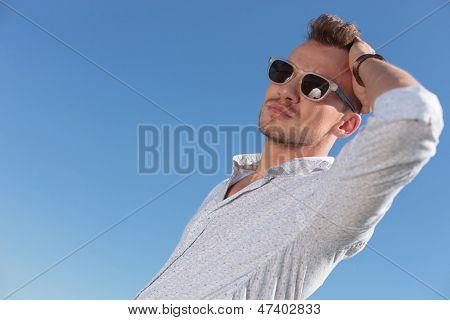 hombre joven informal permanente al aire libre y pasando su mano a través de su pelo mientras mira lejos de la